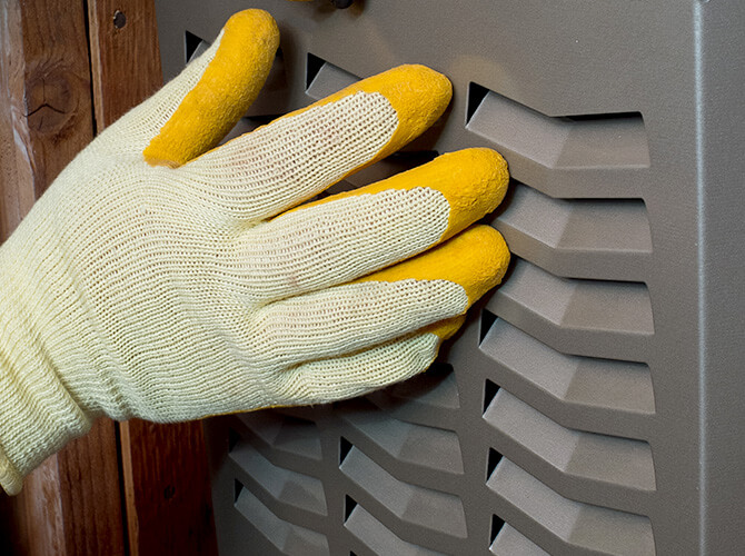 Gloved hand working on an HVAC system